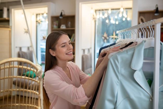 Uma jovem sorridente escolhendo novas roupas da moda