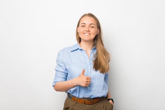 Uma jovem sorridente está olhando para a câmera com um polegar para cima