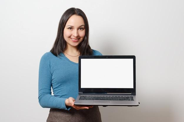 Uma jovem sorridente está segurando um laptop com uma tela em branco branca vazia.