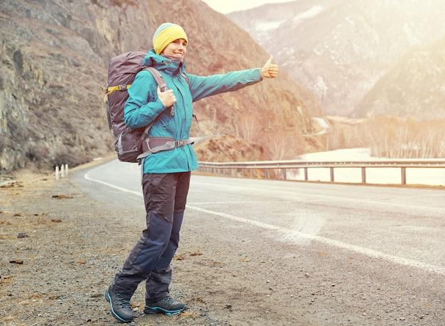 Uma jovem sorridente está viajando nas montanhas. pára o carro na estrada (pedindo carona), levanta a mão.