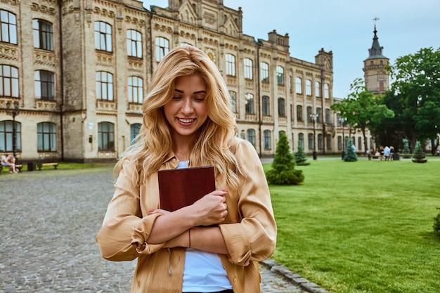 Uma jovem sorridente estudante do ensino médio ou universitária segurando um livro didático