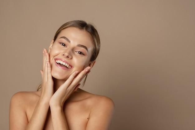 Uma jovem sorridente feliz com uma pele perfeita, maquiagem natural e um lindo sorriso.