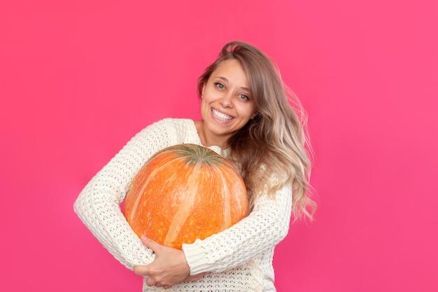 Uma jovem sorridente loira com um suéter branco segura uma grande abóbora nas mãos conceito de halloween