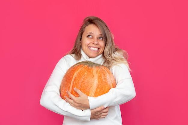 Uma jovem sorridente loira com um suéter branco segura uma grande abóbora nas mãos sobre um fundo rosa