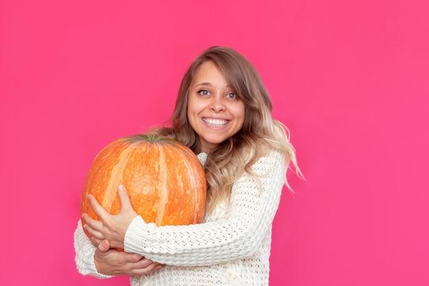Uma jovem sorridente loira com um suéter quente de lã branca segura uma grande abóbora conceito de halloween