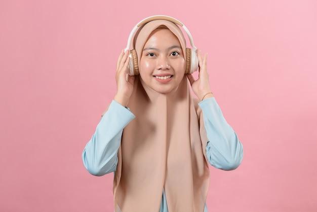 Uma jovem sorridente muçulmana ouve sua música favorita em fones de ouvido brancos, olhe para a câmera, diversão, amante da música, contra fundo rosa