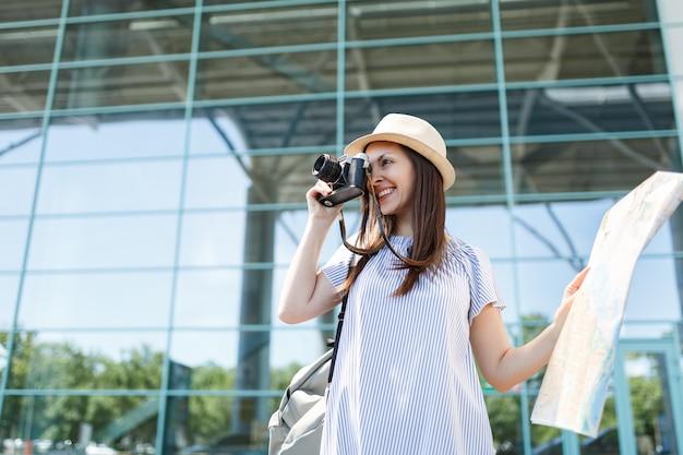 Uma jovem sorridente viajante turista tira fotos em uma câmera fotográfica vintage retrô, segurando um mapa de papel no aeroporto internacional