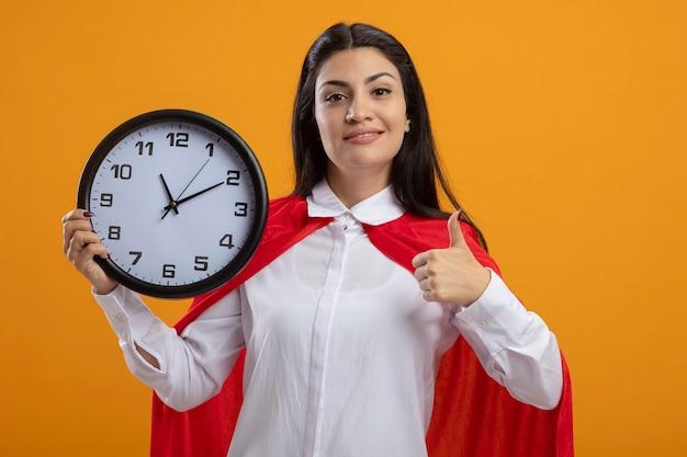 Uma jovem super-heroína caucasiana satisfeita segurando um relógio olhando para a câmera e mostrando o polegar isolado em um fundo laranja