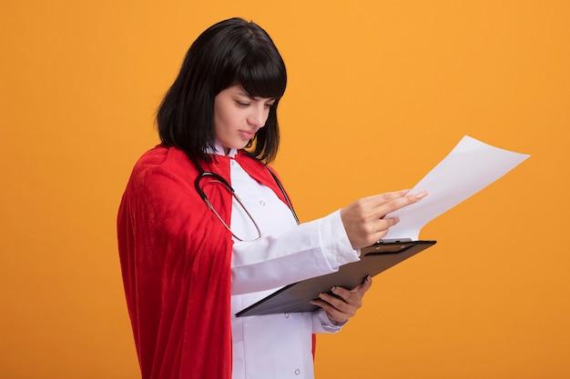 Uma jovem super-heroína satisfeita usando estetoscópio com manto médico e capa folheando a prancheta isolada na parede laranja