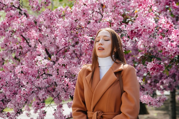 Uma jovem tira a máscara e respira profundamente após o final da pandemia em um dia ensolarado de primavera, em frente a jardins florescendo.