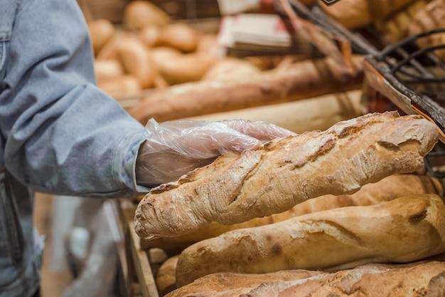 Uma jovem tira do balcão do supermercado pão fresco.