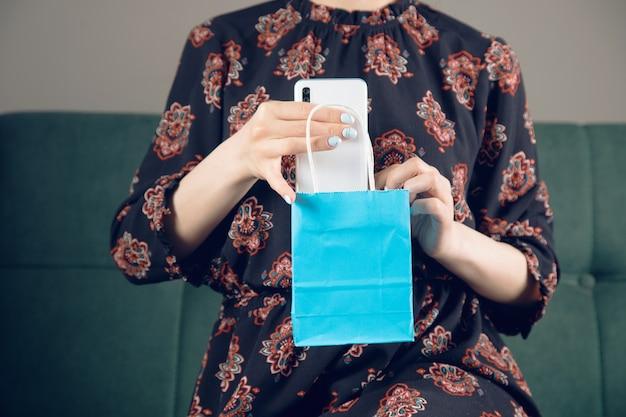 Uma jovem tira um telefone de uma sacola de presentes sentada em um sofá