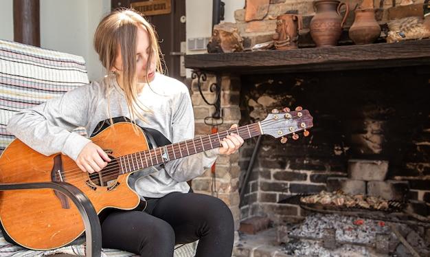 Uma jovem toca violão em um ambiente aconchegante.