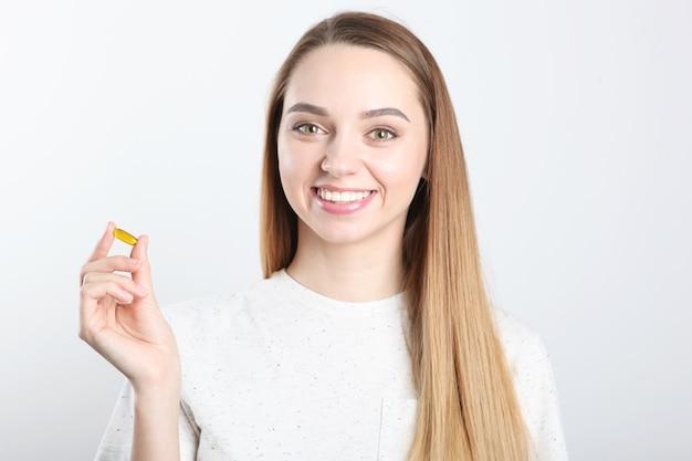 Uma jovem toma cápsulas de ômega, suplementos nutricionais para cuidados de saúde