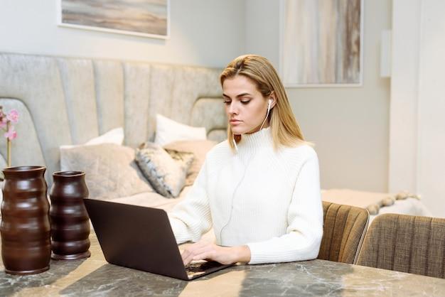 Uma jovem trabalha com um laptop em seu apartamento. a empresária freelance em fones de ouvido está realizando uma reunião de negócios em casa.