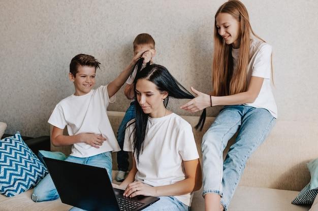 Uma jovem trabalha em casa com um laptop junto com as crianças, as crianças querem se comunicar com a mãe, fazem barulho e atrapalham o trabalho