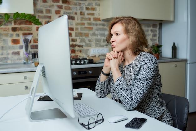Uma jovem trabalha remotamente em um computador desktop em seu estúdio. uma senhora senta os braços cruzados durante uma videoconferência em casa.