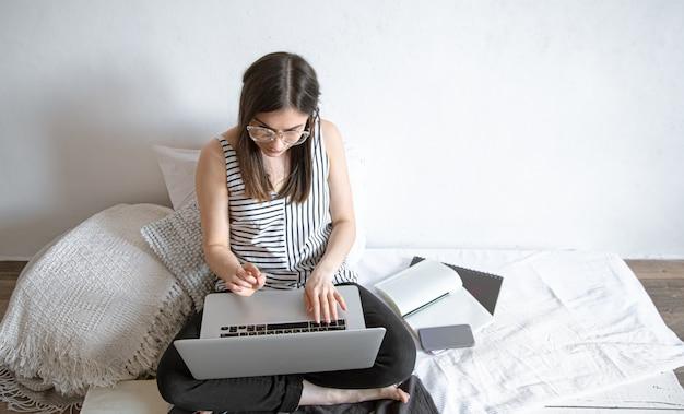 Uma jovem trabalha remotamente em um computador em casa. freelancer e trabalho na internet.