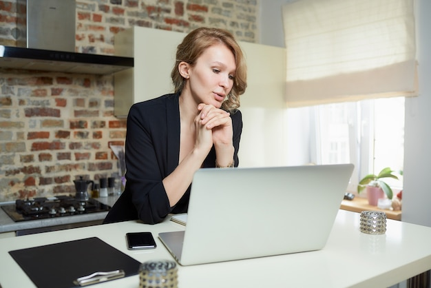 Uma jovem trabalha remotamente em um laptop em uma cozinha. uma garota encantadora discutindo o relatório de um colega em uma videoconferência em casa. uma professora se preparando para uma palestra on-line.