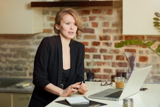 Uma jovem trabalha remotamente em um laptop na cozinha dela. uma chefe do sexo feminino se decepcionou com seus funcionários durante uma videoconferência em casa.