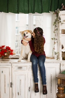 Uma jovem triste com um cão obediente senta-se em uma cômoda perto da janela