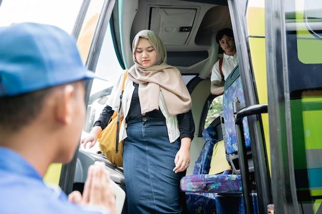 Uma jovem turista asiática com mochila saindo do ônibus de viagem
