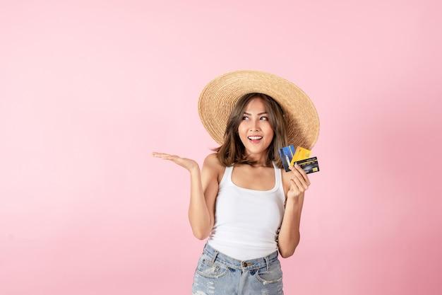Uma jovem turista asiática vestindo roupas de verão ela segurou um cartão de crédito e apontou para o espaço