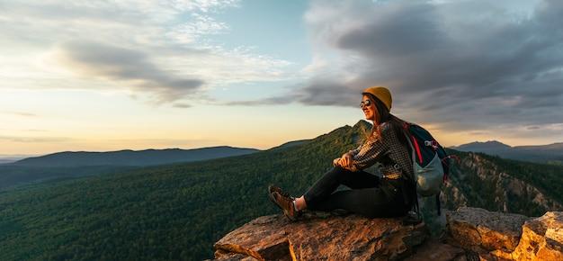 Uma jovem turista com uma mochila aprecia o pôr do sol do topo da montanha. um viajante no fundo das montanhas. um viajante no fundo das montanhas ao pôr do sol, vista panorâmica.