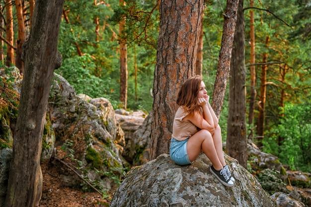 Uma jovem turista está caminhando em uma floresta densa com pedras enormes e musgo