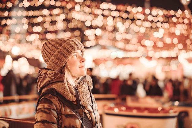 Uma jovem turista está de pé e sorrindo na rua à noite na cidade