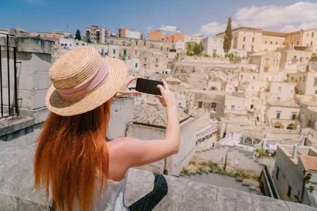 Uma jovem turista fotografa o panorama de uma antiga cidade europeia