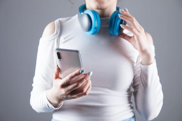 Uma jovem usa fones de ouvido grandes e mantém seu telefone em um cenário cinza