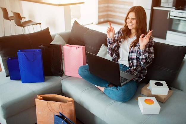 Uma jovem usa um laptop e compra muitos produtos na internet nas vendas online.