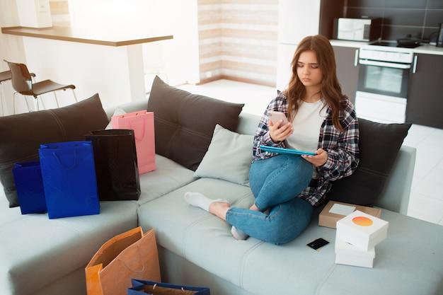 Uma jovem usa um tablet pc e compra muitos produtos na internet em vendas on-line