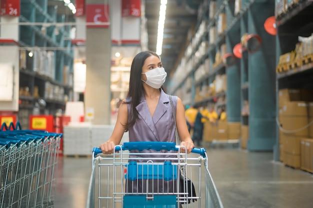 Uma jovem usando uma máscara cirúrgica com um carrinho em um shopping center, covid-19 e conceito de pandemia