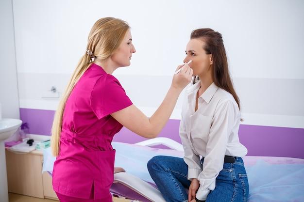 Uma jovem veio à clínica para uma consulta com um médico qualificado, um cosmetologista especialista. o médico examina a condição da pele do rosto do paciente