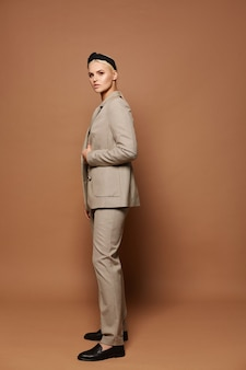 Uma jovem vestindo roupas de estilo oficial isoladas em um fundo bege modelo loira em um terno moderno isolada no fundo com espaço de cópia