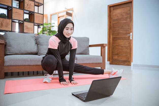 Uma jovem vestindo uma roupa de ginástica hijab ao se agachar se alonga com uma perna puxada para o lado enquanto está na frente de um laptop na casa
