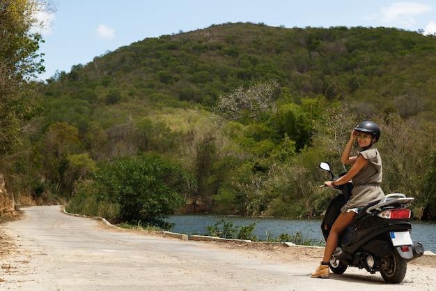 Uma jovem viajante está dirigindo uma scooter na velha estrada rural nas montanhas