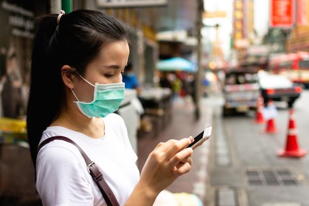 Uma jovem viajante usando máscara protetora médica está usando um telefone inteligente em uma cidade grande
