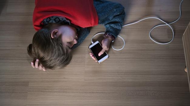 Uma jovem viciada em celular dorme no chão da sala.