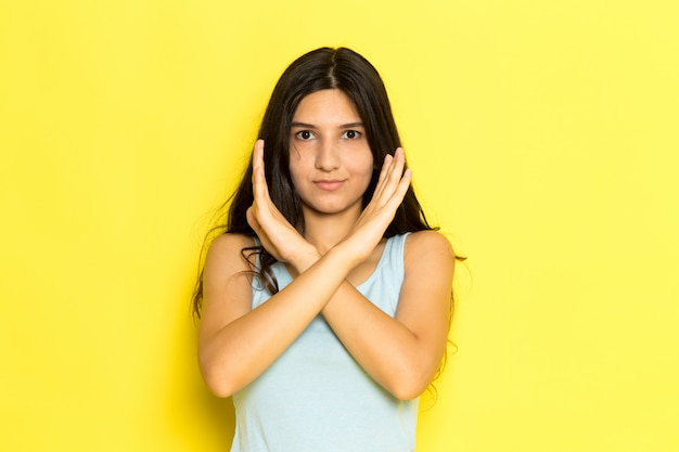 Uma jovem vista frontal com camisa azul posando showign sinal de proibição no fundo amarelo garota pose modelo beleza jovem
