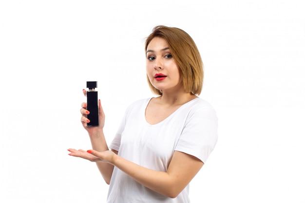 Uma jovem vista frontal em t-shirt branca segurando o tubo de perfume preto no branco
