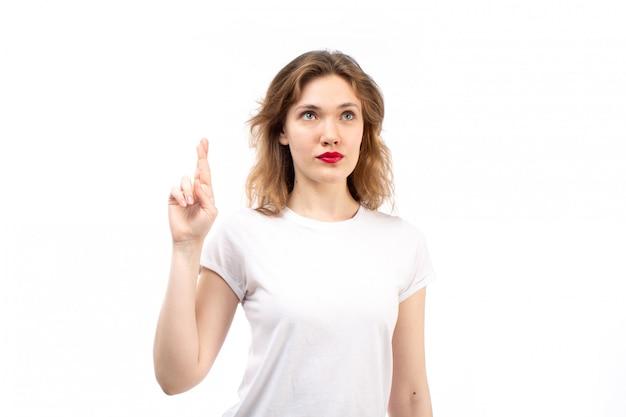 Uma jovem vista frontal na camisa branca e calça jeans moderna preta posando pensando no branco