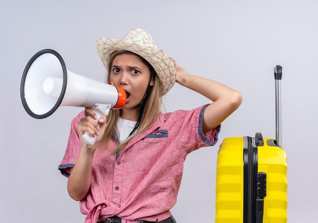 Uma jovem zangada com uma camisa vermelha e um chapéu de sol falando através do megafone com as mãos na cabeça