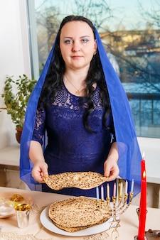 Uma judia morena com a cabeça coberta por uma capa azul na mesa do seder da páscoa quebra a matzoh shmura. foto vertical