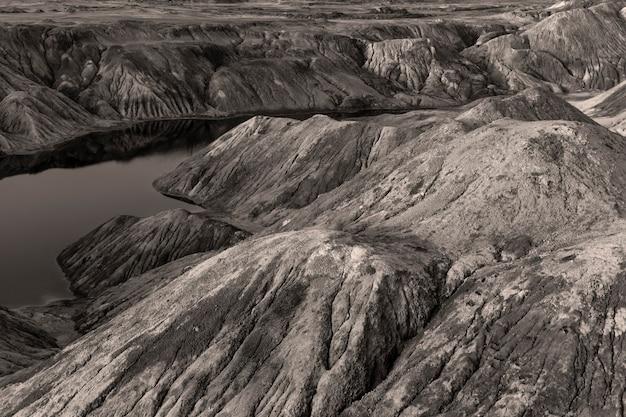 Uma lagoa - um lago ou um rio - com água vermelha em um desfiladeiro entre colinas desertas de areia