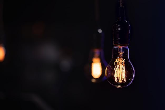 Uma lâmpada acesa está pendurada no escuro sobre um fundo desfocado.
