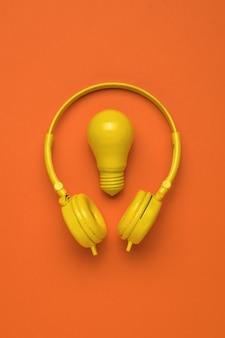 Uma lâmpada amarela e fones de ouvido amarelos em um fundo laranja. minimalismo. postura plana.