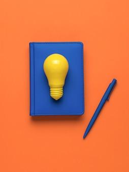 Uma lâmpada amarela, um caderno com uma caneta em um fundo laranja. postura plana.